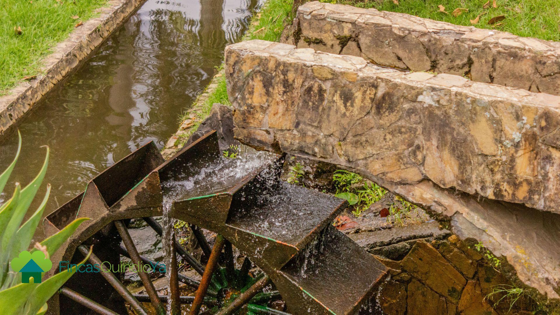 Molino al cual le cae agua de un conducto en El Parque de la Vida de Armenia