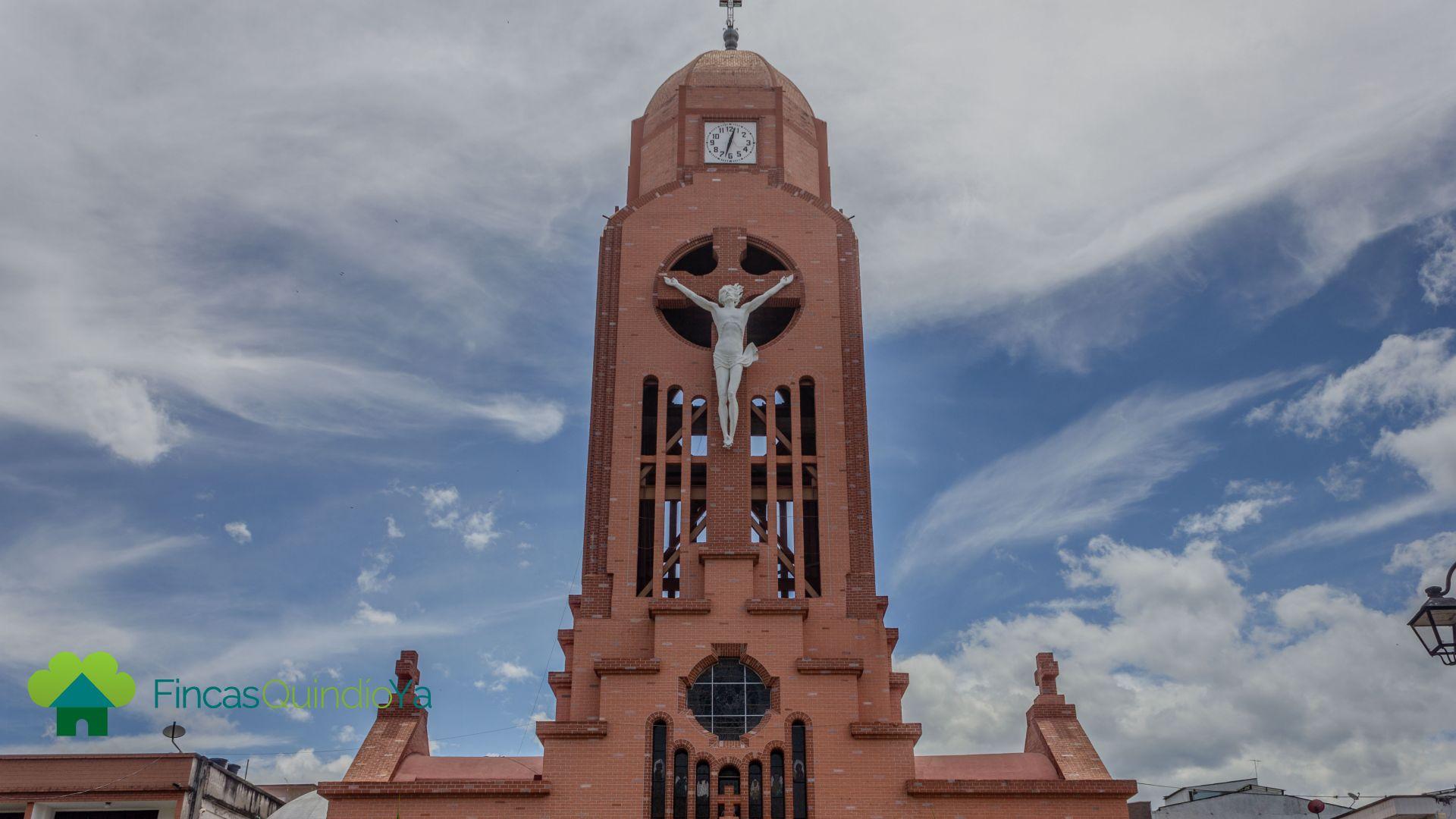 Foto a iglesia que tiene un jesus gigante en una cruz en su fachada